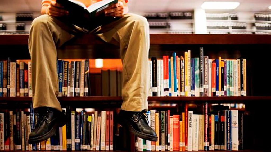 Man sitting on library shelf reading book.
