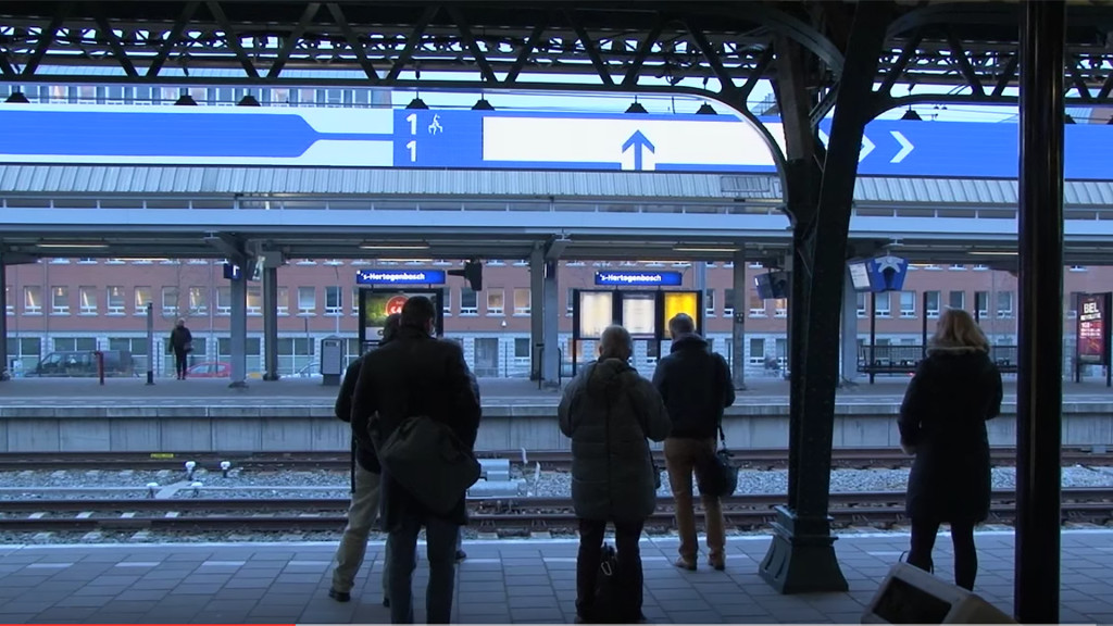 People waiting on a train platform, looking at a large screen with info about the composition of the train.