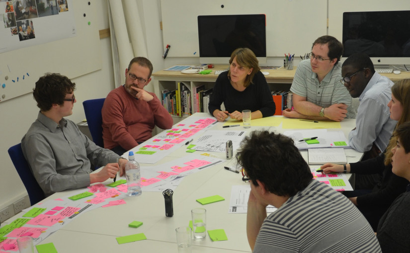 Group of people around a table full of papers and post-its and workshop materials.