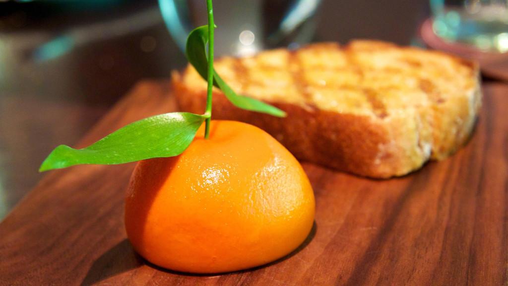 Orange and toast on wooden surface