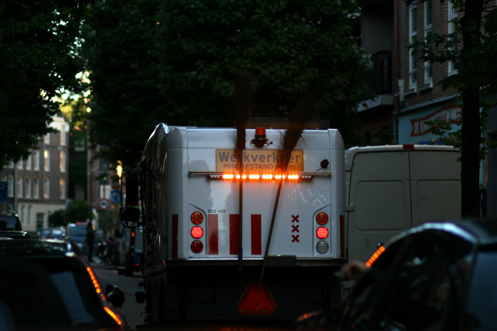 street cleaning truck on street, seen from behind