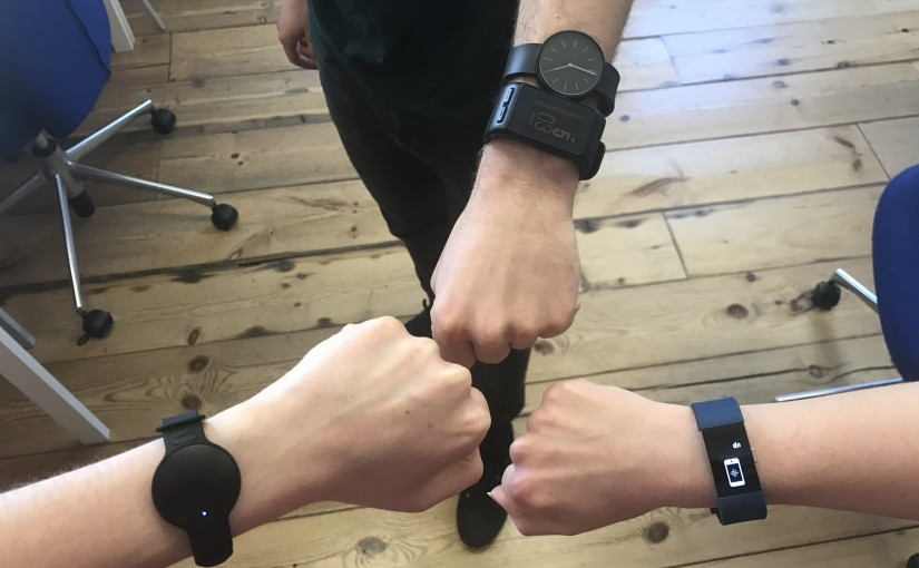 three people showing wrists together with smartwatches on