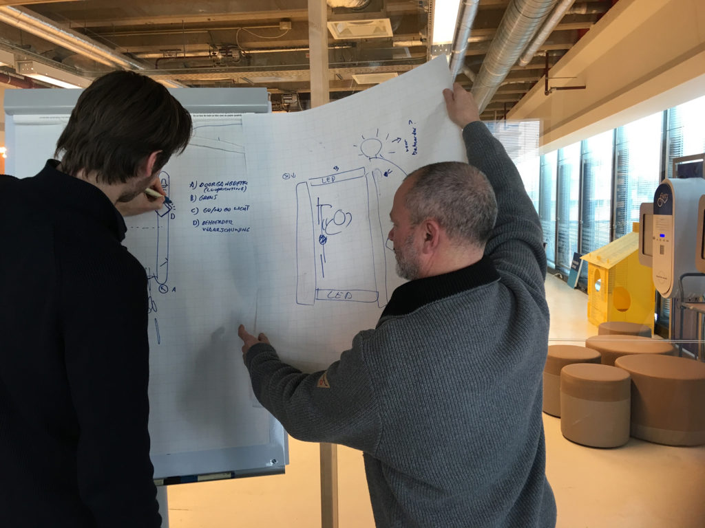 Two designers holding a drawing and sketching.