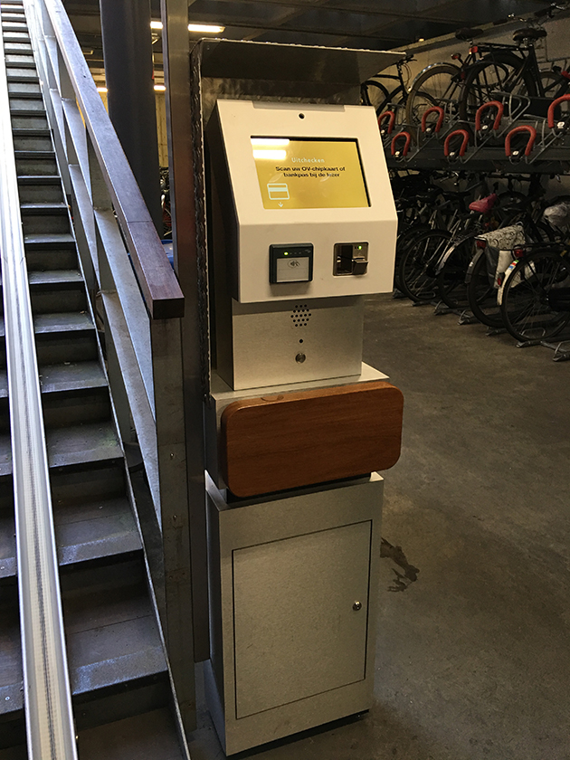 Machine for paying for bike parking next to staircase.