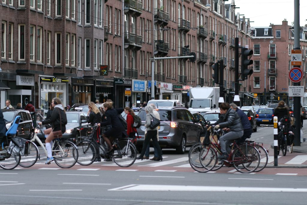 busy street with bikes and pedestrians and cars