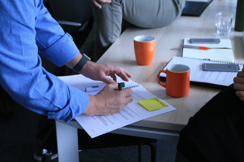 hand with pen taking notes in meeting